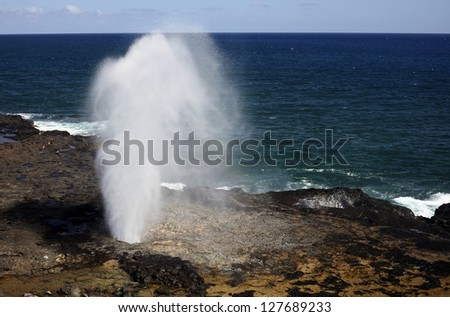 "A ""spouting horn"" is created by Pacific Ocean wave action along the volcanic rock coast of Kauai, Hawaii. - stock photo"