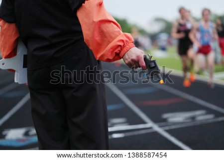 A race official fires a starters gun, indicating the final lap of the race