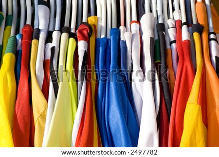 A rack of colorful shirts (Jerseys) for sale at an open market