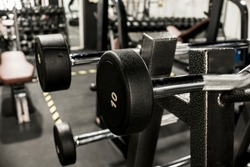 A rack of EZ and straight bar barbells with fixed weights at a gym or fitness club.