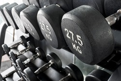 A rack of heavy dumbbells with weight labels in kilograms at the gym. Weight training equipment.