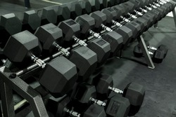 A rack of heavy hex dumbbells at a gym or fitness club. Workout and pyramid training or running the rack for serious bodybuilding concept.