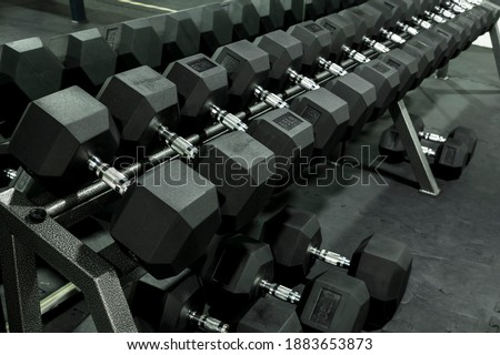 A rack of heavy hex dumbbells at a gym or fitness club. Workout and pyramid training or running the rack for serious bodybuilding concept. Stock photo ©
