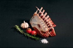 A rack of new Zealand Lamb in raw form on a black background
