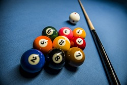 A rack of nine ball for Qatar tournament, European championship, with 9 balls on a blue cloth and a billiard cue and white spoted cue ball with red dots, ready to play a game