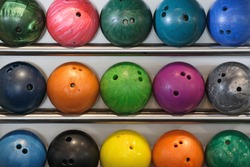 A rack of old worn bowling balls.