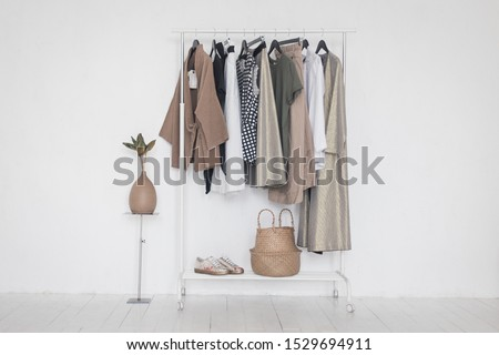 A rack with stylish clothes next to a white wall in the room. Clothing retails concept. Advertise, sale, fashion. Сток-фото ©