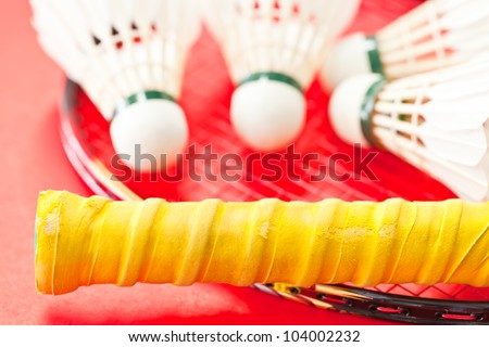a racket and shuttlecock on red