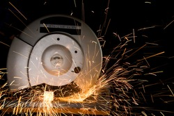 A radial arm saw slices through metal square stock, casting a stream of sparks.