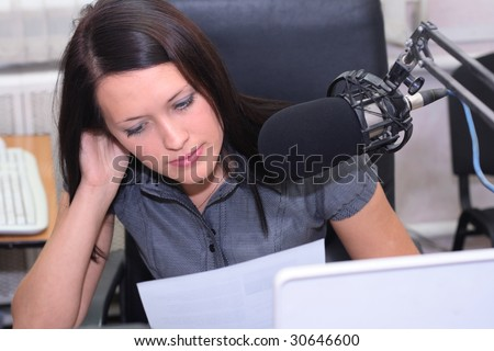 A radio DJ is in front of the mic in broadcasting studio