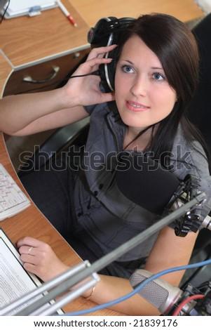 A radio DJ is listening to music with headphones in studio