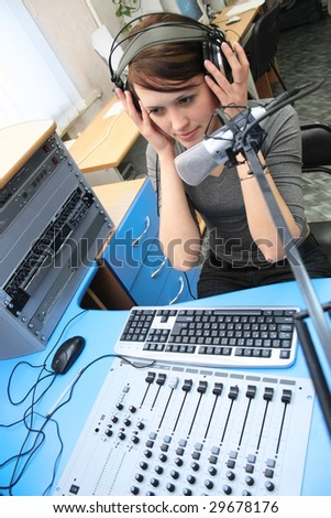 A radio DJ with headphones in the broadcasting studio