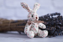 A rag rabbit sits in a delicate interior next to a lavender bouquet. Children's room. Decor elements.