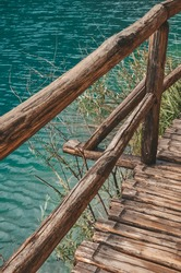 A railing of a wooden bridge over blue water and green grass, Plitvice Lakes in Croatia