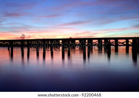 a railroad bridge crossing a river before sunrise