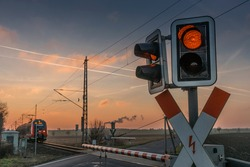 A railroad crossing in a landscape with a train