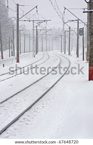A railroad line covered with snow in a winter day