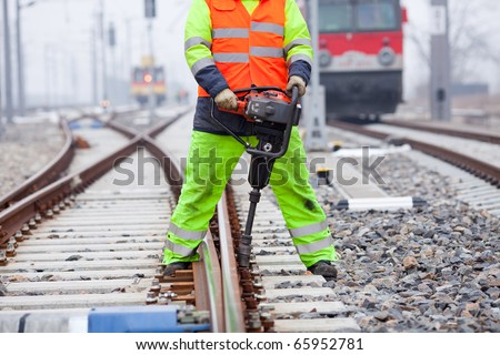 a railroad worker unscrews a screw on the rails