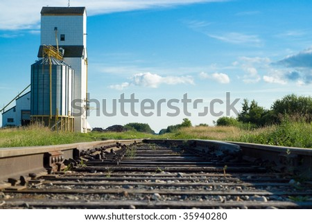A railway going to a prairie grain elevator shot on a partly cloudy day
