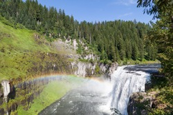 A rainbow in the mist of Upper Mesa Falls as it cascades over a cliff in the rugged wilderness of Henrys Fork of the Snake River along the Mesa Falls Scenic Byway in Idaho.