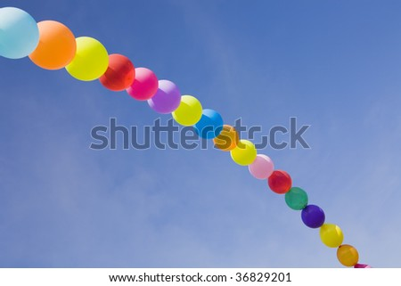 A rainbow made with coloured baloons in the sky