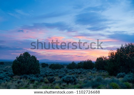 A rainbow of painted clouds above a Pinyon-juniper woodland on Arizona Strip District BLM Land, Coconino County, Arizon, USA.