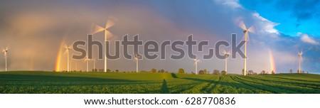 a rainbow over a wind farm on a ...