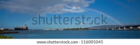 A rainbow spans Pearl Harbor from the bridge to a military ship. The USS Arizona memorial is below. Oahu, Hawaii