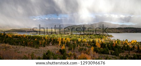 A rainy afternoon with pockets of sunshine on Dillon Reservoir, near Dillon and Silverthorne, Colorado. Fall colors are starting to peak in the aspens.