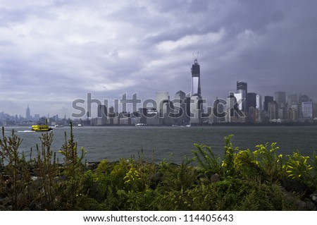 A rainy, cloudy sky is over Manhattan buildings. The front ground is wild yellow flowers growing in rocks/Dramatic rain cloudy sky over New York City