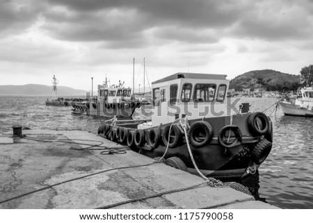A rainy wintry day under a heavy sky. Fishing boats at the small harbor. Pachi,Greece #1175790058