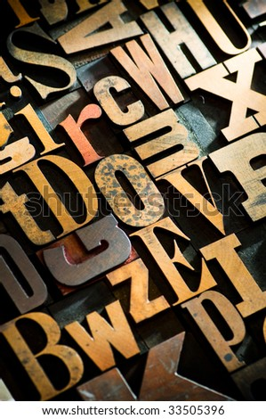 A random selection of wooden letterpress characters as a background, narrow focus.