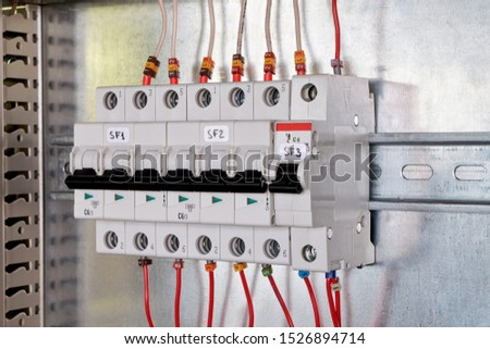A range of modular circuit breakers in an electrical Cabinet. The switches are connected to the electrical network by wires and marked with digital and letter markings. Electricity distribution. #1526894714