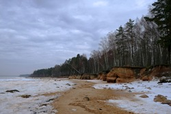 A rare and peculiar natural landscape - a sandstone rocky shore by the frozen Baltic Sea