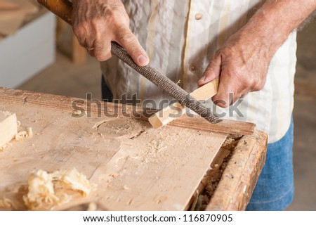 A rasp in the  rugged hands of a skilled carpenter