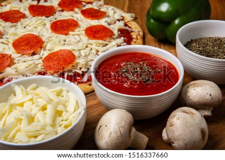 A raw pizza and all the ingredients that made it.