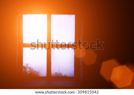 A ray of morning sun in an old window