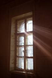 A ray of sun coming through an old window. Concept of hope.