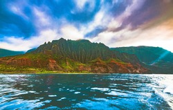 A ray of sunlight beams down during sunset on Honopu and Kalalau beach, part of the colorful and dramatic Nā Pali Coast State Wilderness Park on the island of Kauai, Hawaii, United States.