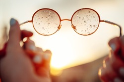 A ray of sunshine glitters on the glass of glasses, shading off drops of water. Raindrops on the glasses. Sunglasses in the hands of the girl. Summer rain.