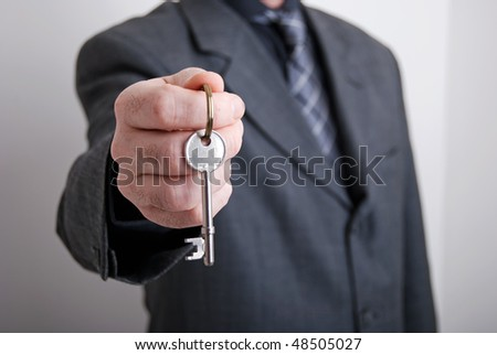 A real estate agent holds out the front door key of a new home to a lucky buyer.