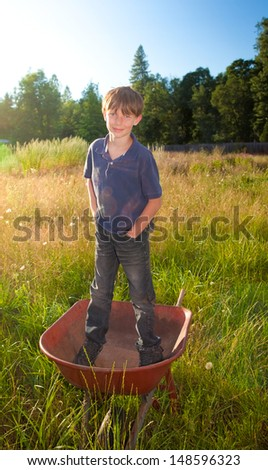 A real life young boy, with a faded shirt and dirty jeans, standing in a wheelbarrow in rural landscape.