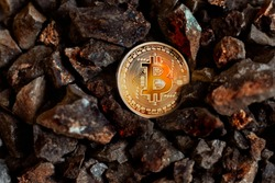 a real textured 3d yellow bitcoin coin between some golden rocks