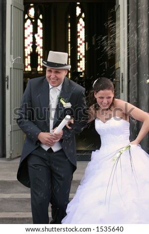 stock photo A real wedding bride and groom walking out the churchdoor