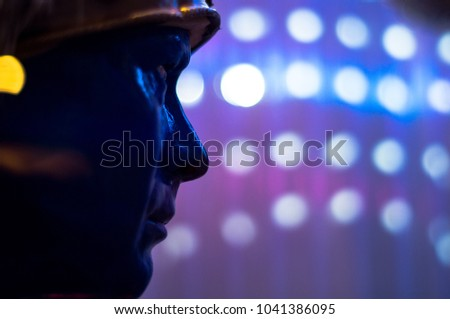 A realistic blue mannequin head with flashing lights in the background. #1041386095