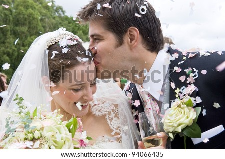 A really happy looking bride and groom being showered with confetti by their guests