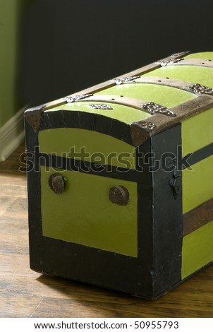 A really old Steamer Trunk setting on an old wooden plank floor with a dark background,