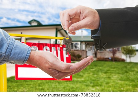 A  realtor handing over keys to a buyer in-front of a house - stock photo