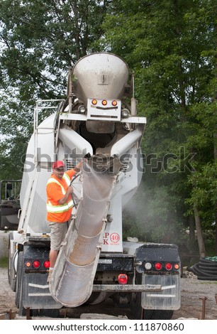 A rear view of a cement truck being readied by its operator to pour cement down the chute. - stock photo