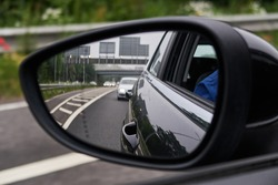 A rear view of a highway motorway, seen through the glass of a rear view mirror on an automobile car. Gloomy polluted city sky and vehicle backdrop. Driving a car fast on the city streets.